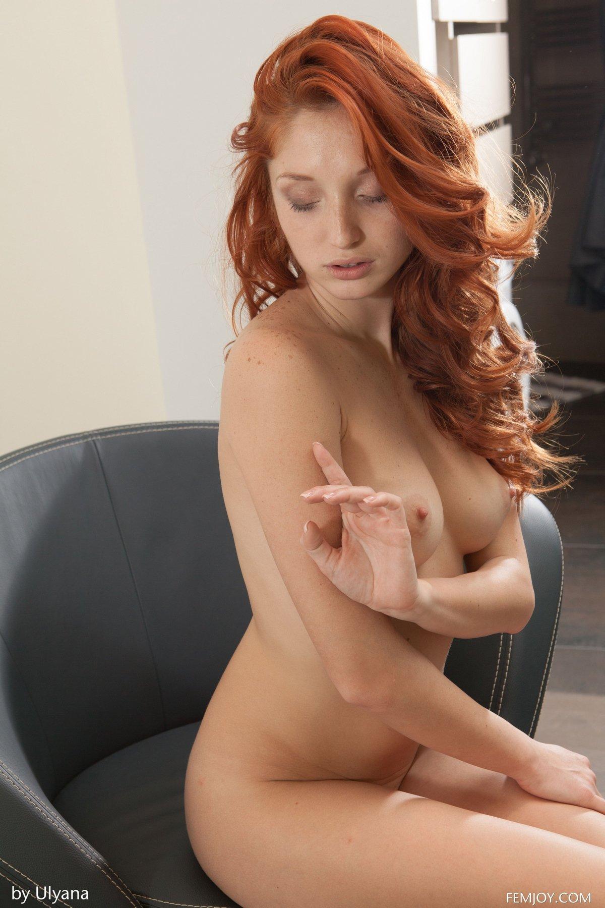 Сексуальная девушка с рыжими волосами в кожаном кресле