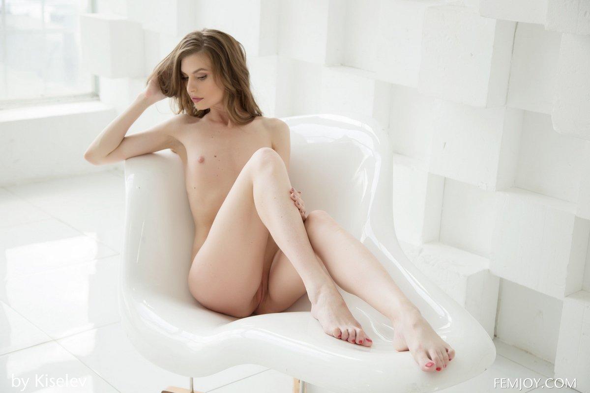 Изящная девушка в белом кресле голая