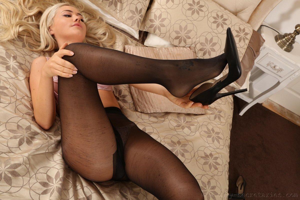 Светловолосая телка в чёрных чулках на кроватке секс фото
