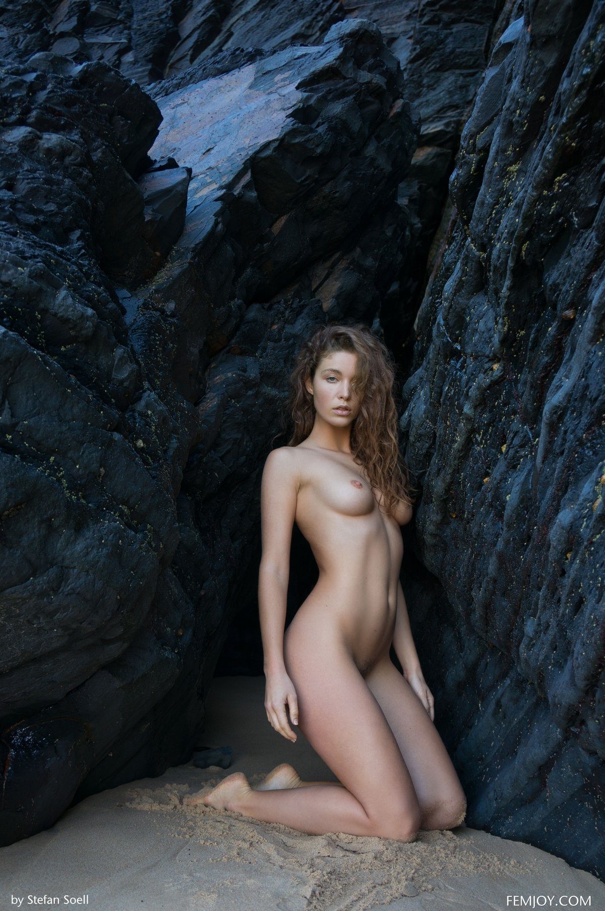 Голая дама с идеальными буферами на фоне черной скалы