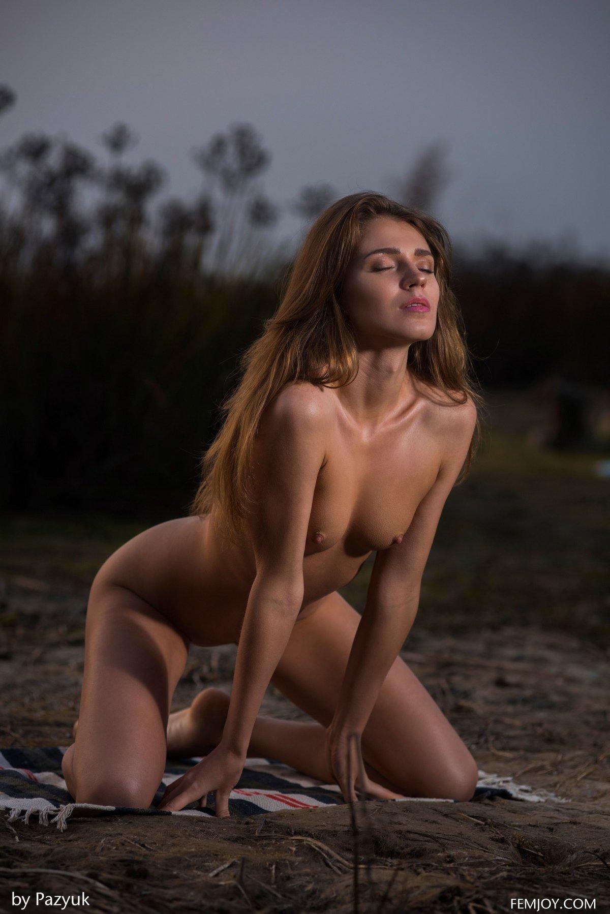 Худенькая девушка в трусиках на берегу реки