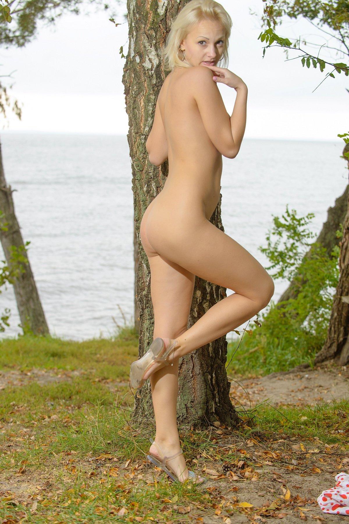 Няшка модель со свелыми волосами растопыривает ноги под деревом