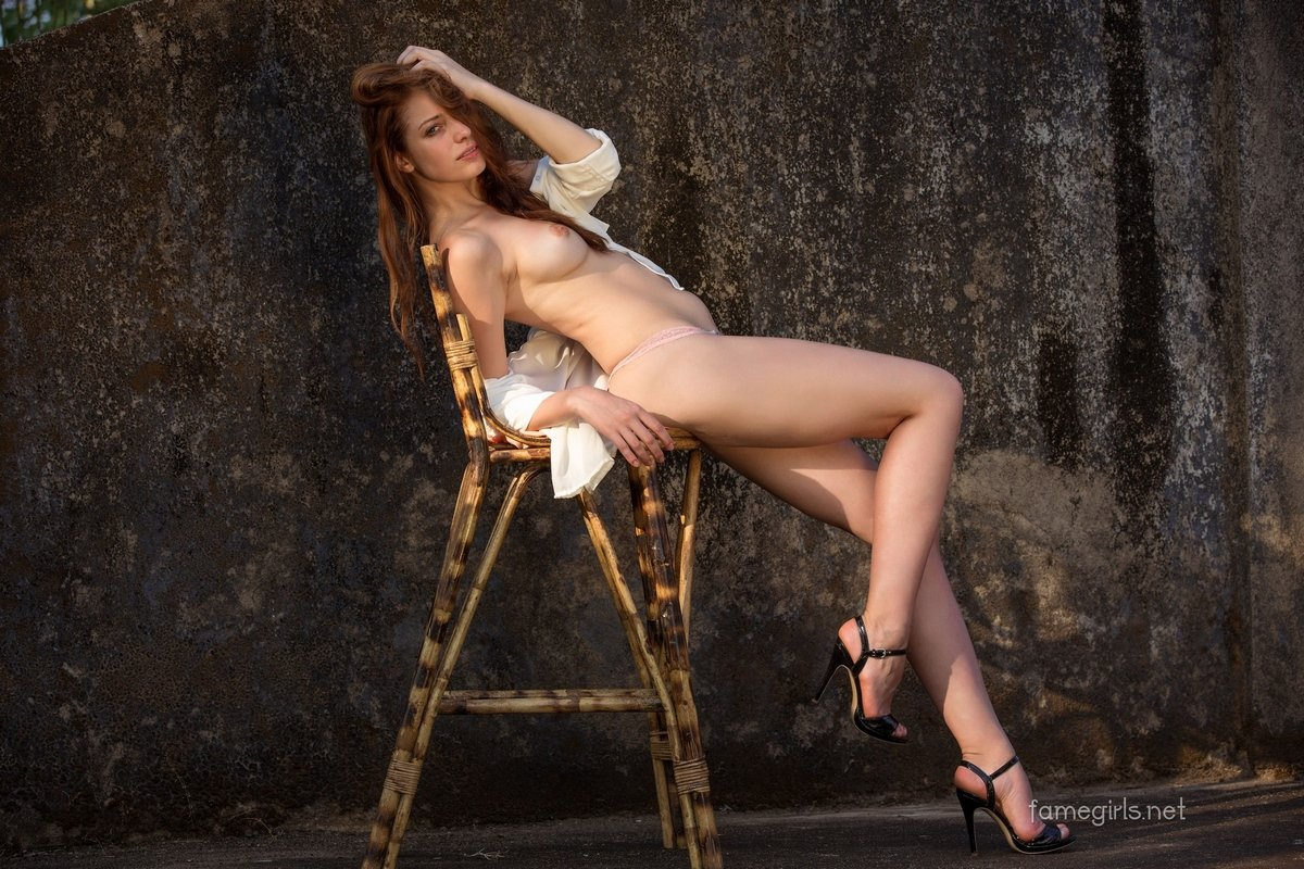 Девка Isabella обнаженная на высоком стуле