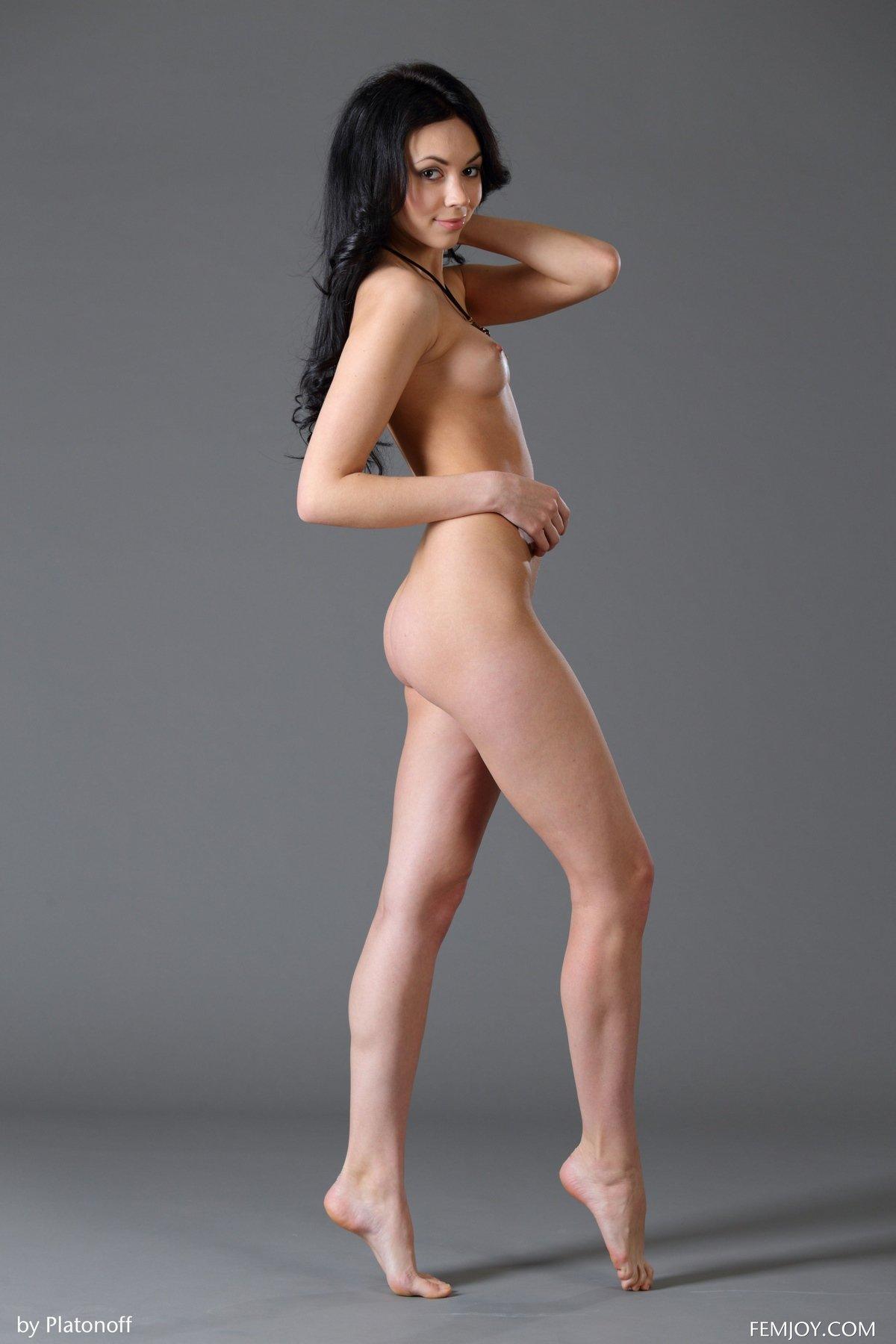 Стройняшка темненькая девушка с длинными волосами фотографируется в студии