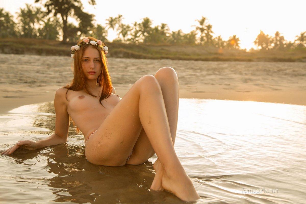 Рыжая девушка с венком в волосах на пляже