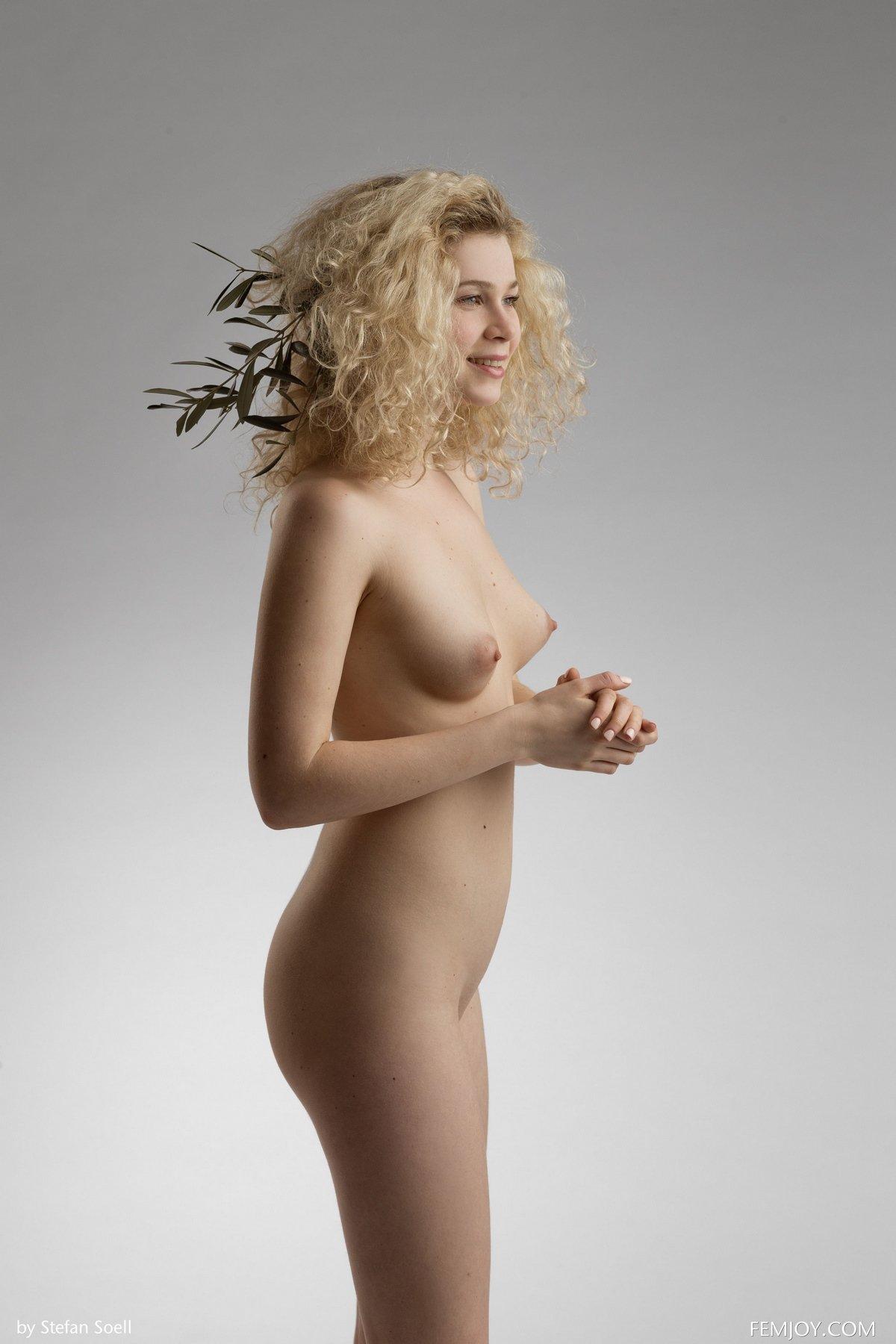 Блондинка красиво позирует с зеленой веточкой