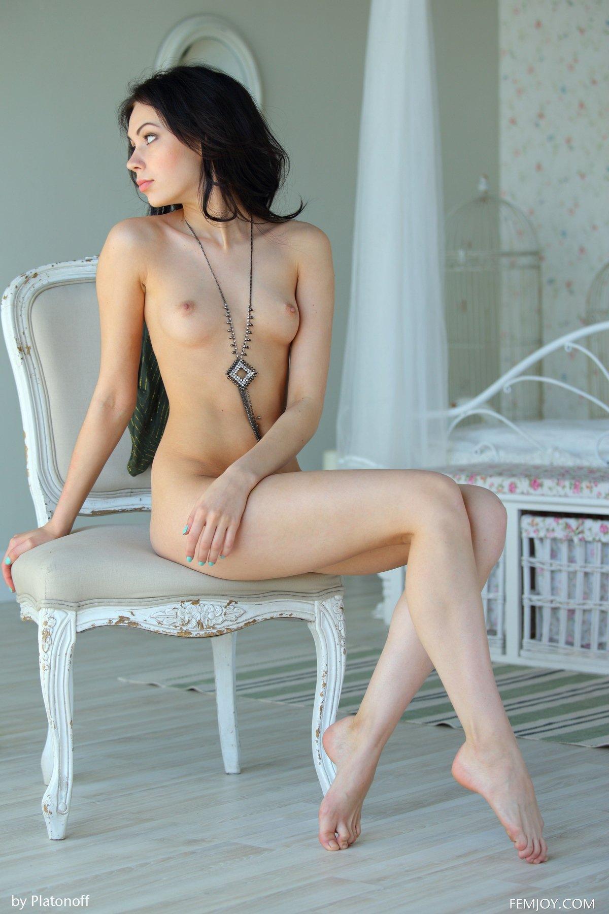 Молодая брюнетка голая на стуле