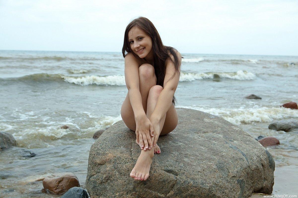 Чика стягивает джинсы на пляже