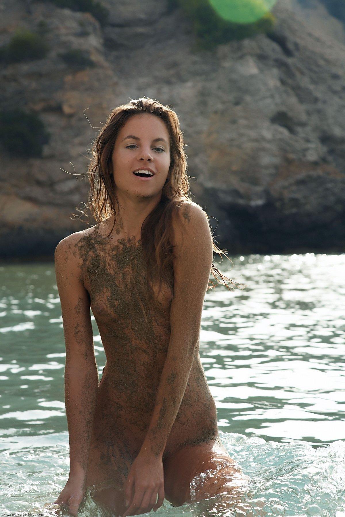Модель с маленькой грудью в мокром песке обнаженная в воде