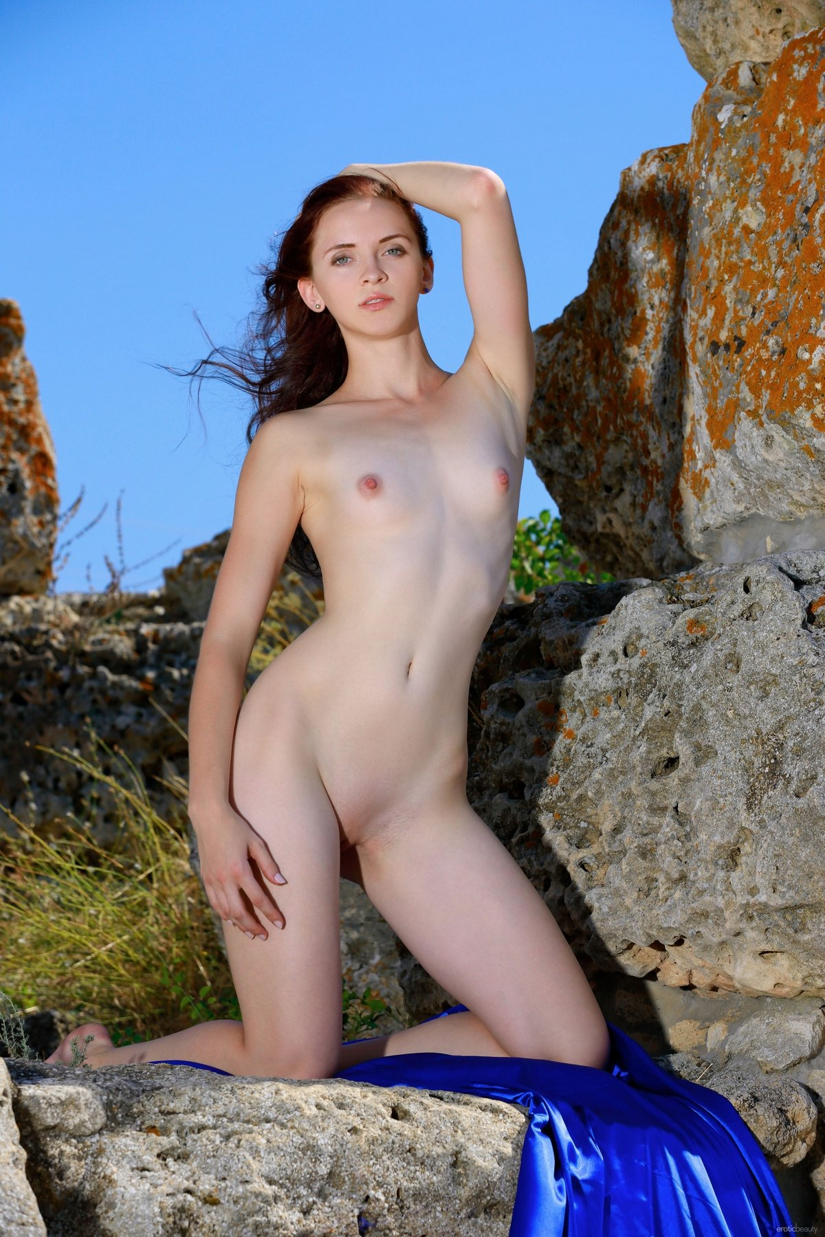Телка с плоской грудью и розовыми сосками торчком возле скалы