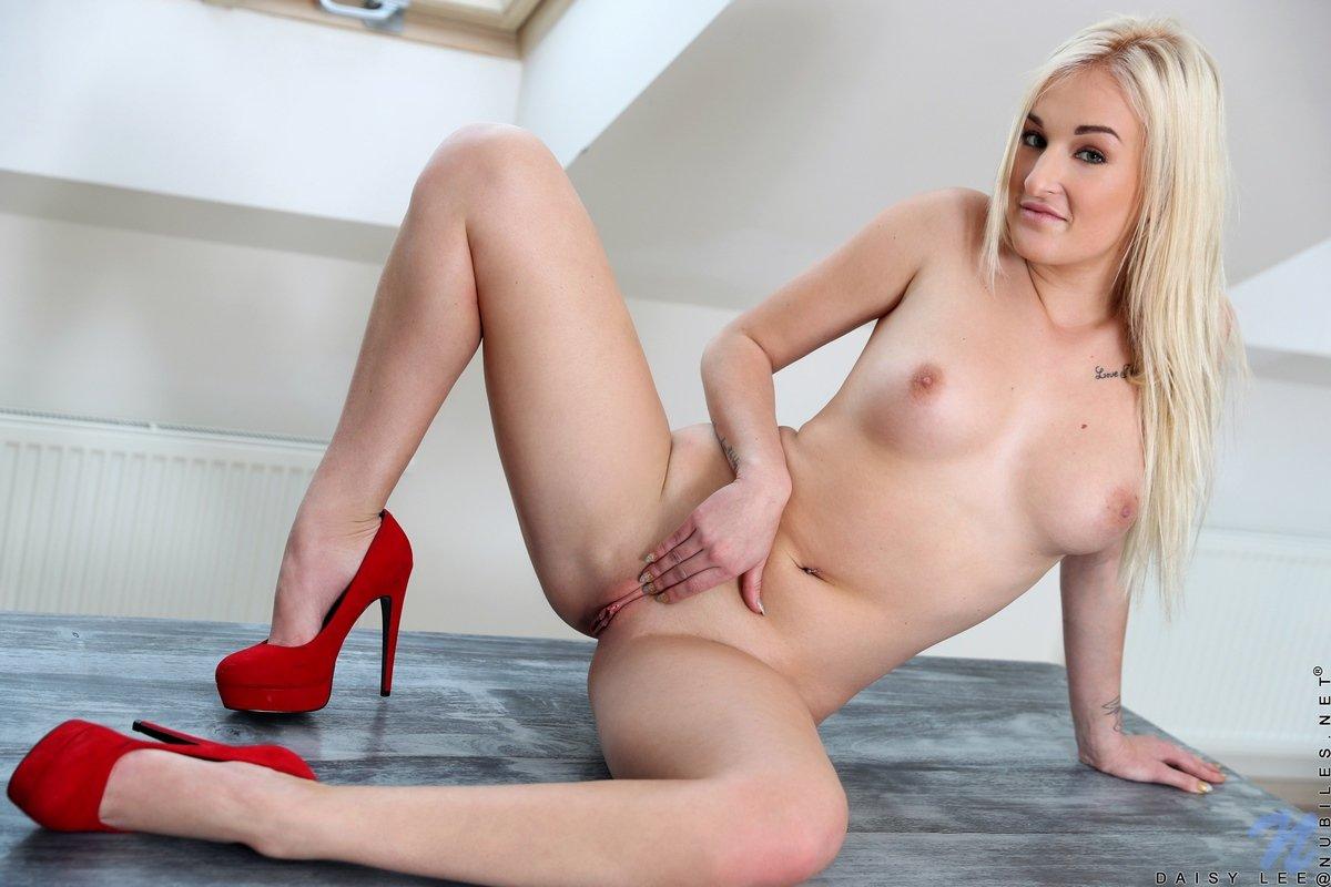Нагая светлая порноактриса в красных туфлях на столе