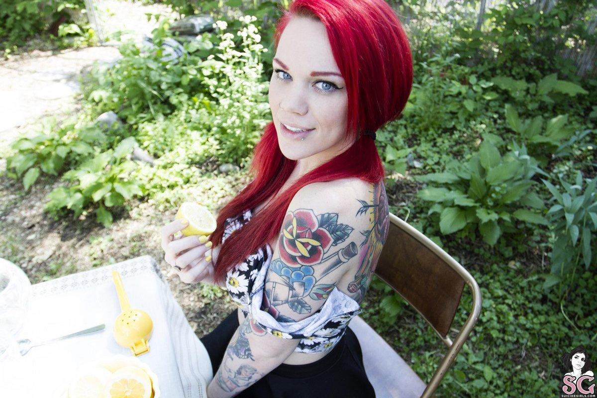 Девушка с большой татуировкой на спине голая в саду