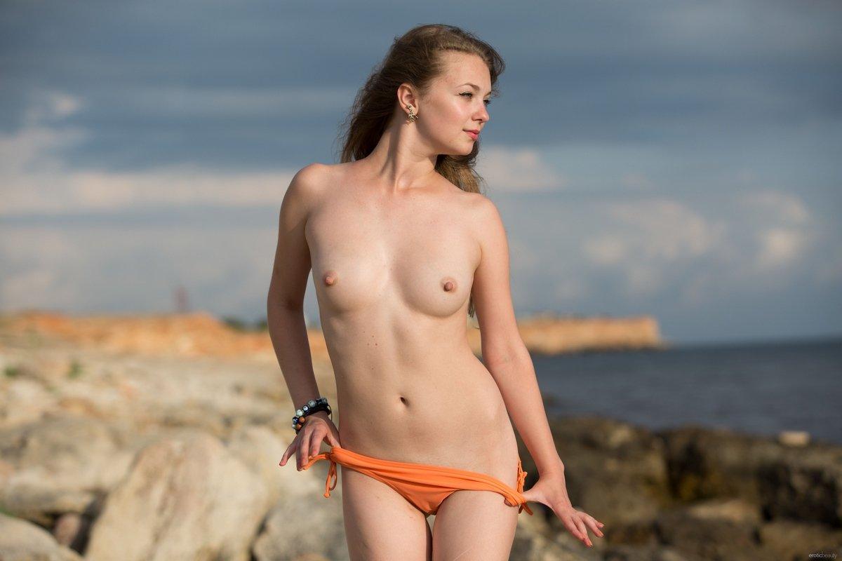 Девушка в оранжевом купальнике на каменистом берегу