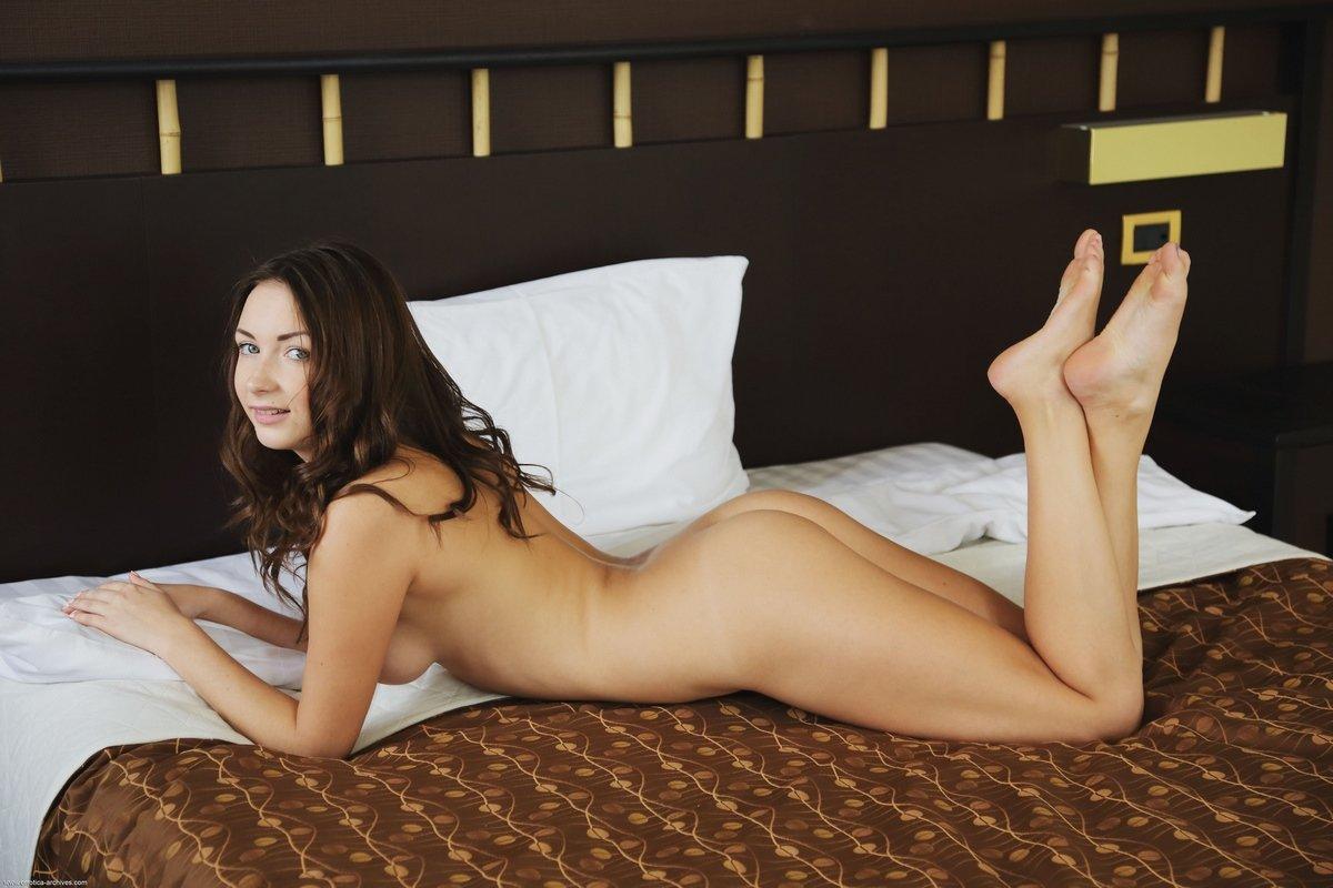 Темноволосая модель показала бритую киску на кровати