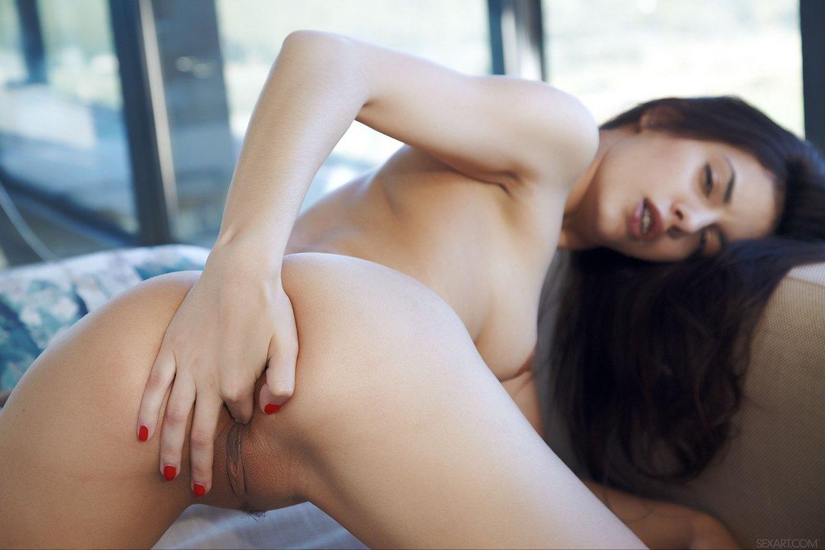 Раздетая брюнеточка гладит темные половые губы