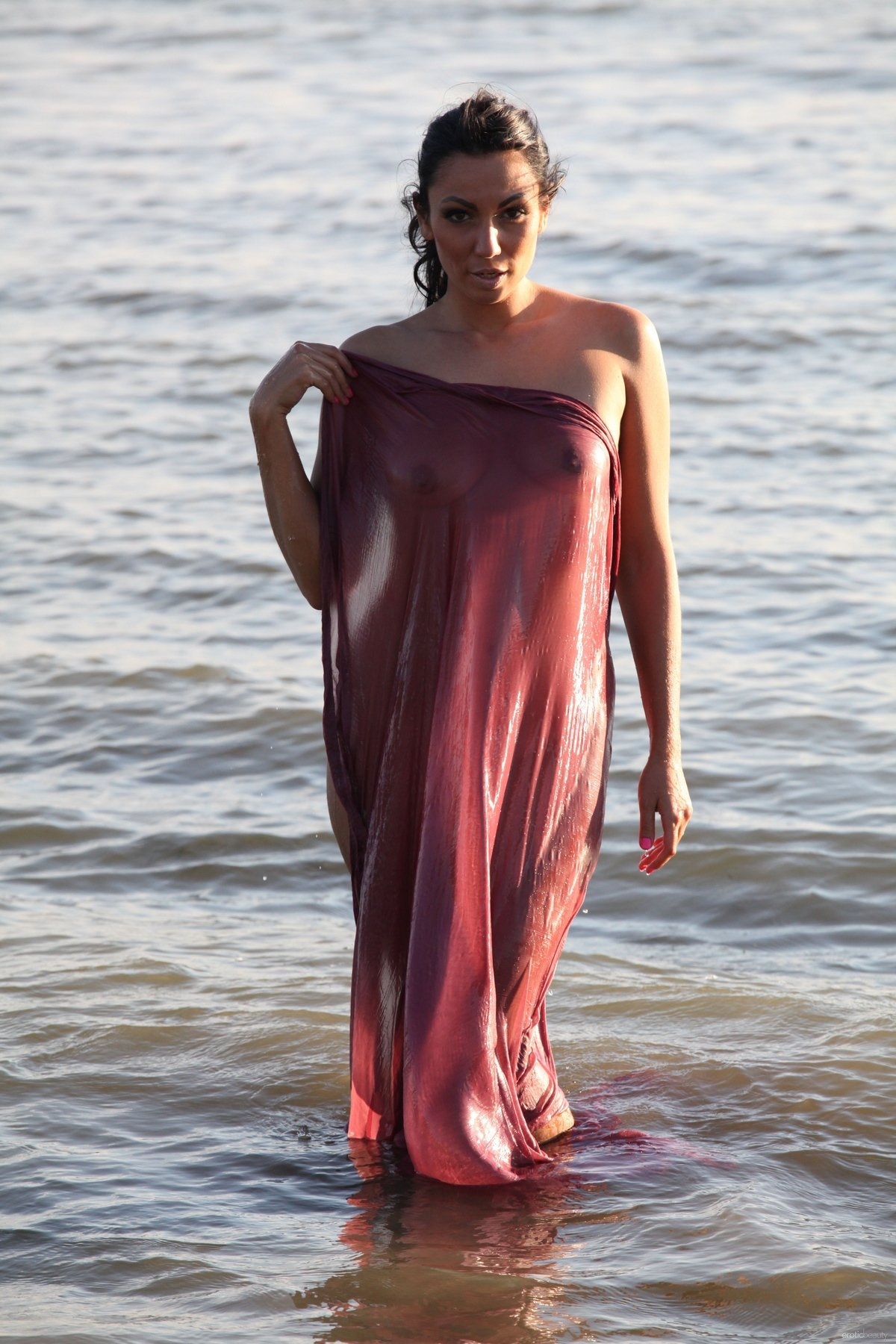 Брюнетка с женственной фигурой играет с парео на берегу реки