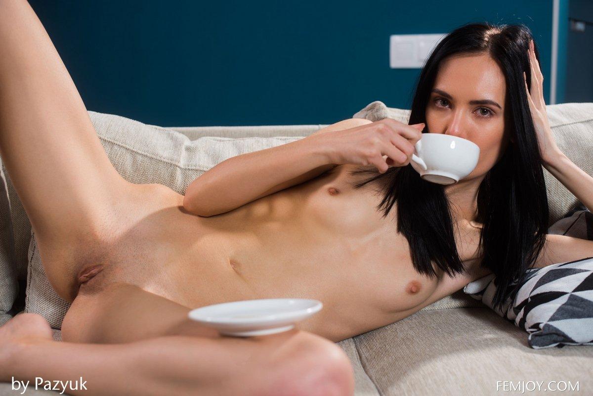 Модель с темными волосами с маленькими буферами пьет чай раздетая