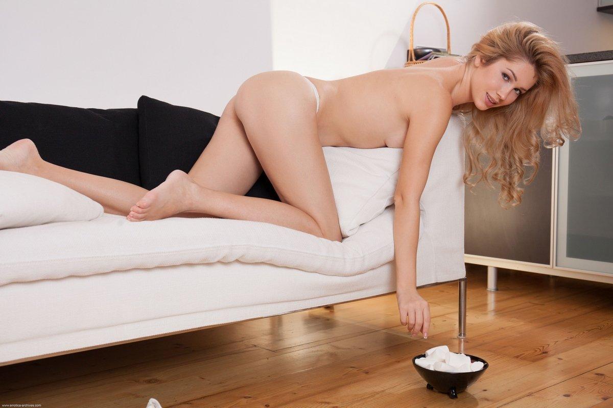 Красивая блондинка ест сладости голая