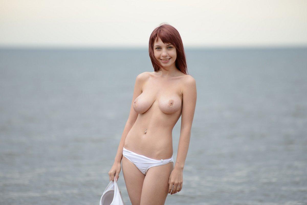 Девушка с красивой грудью снимает купальник на пляже