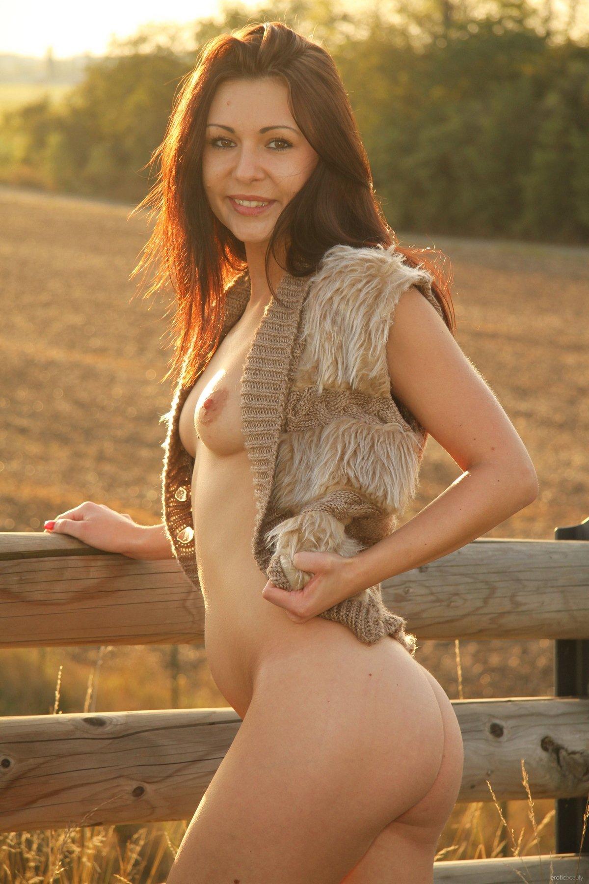 Девушка без трусиков возле изгороди