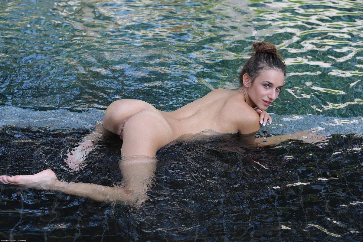 Симпатичная тёлка купается в бассейне обнаженная