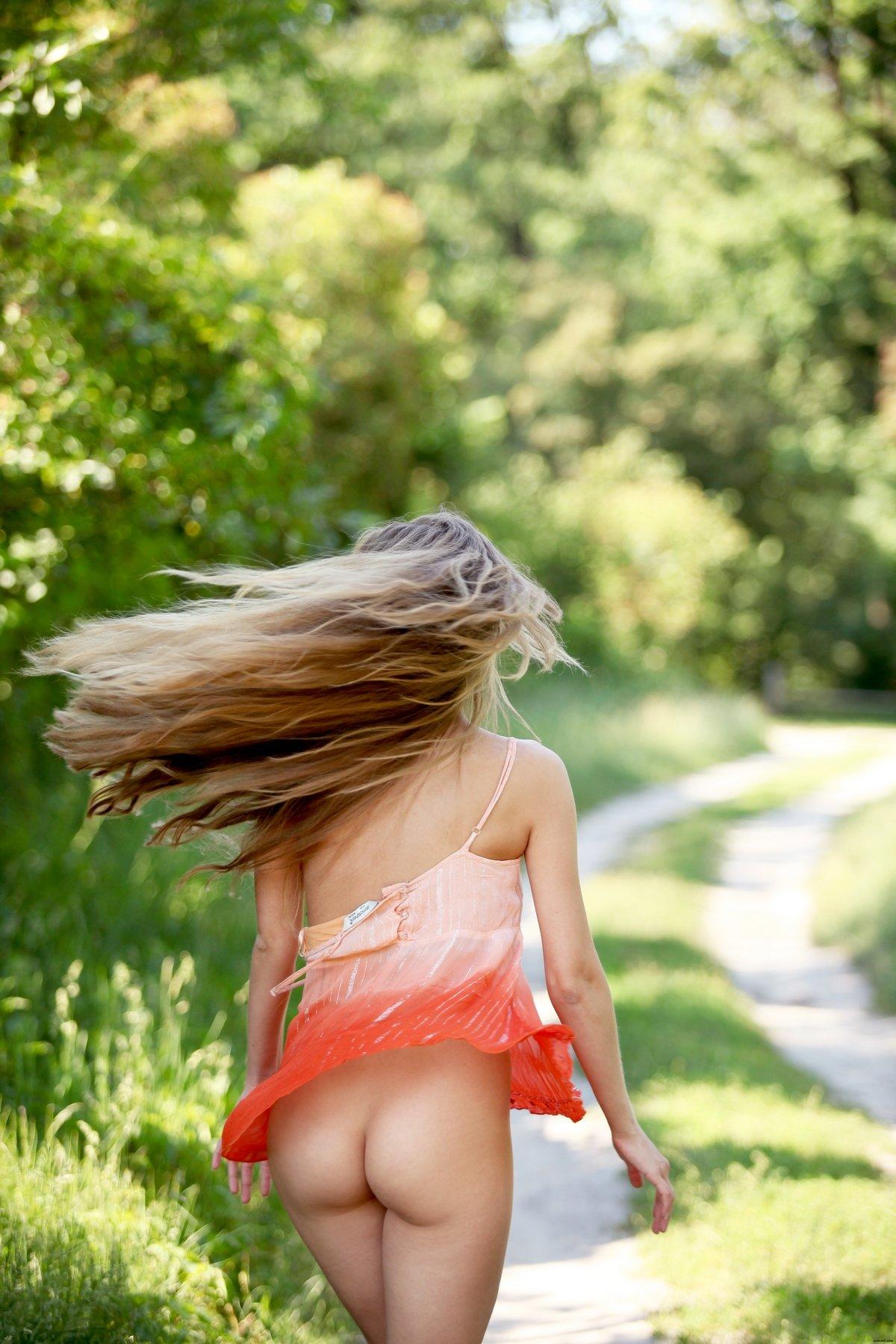 Блондинка с длинными волосами снимает трусики на тропинке