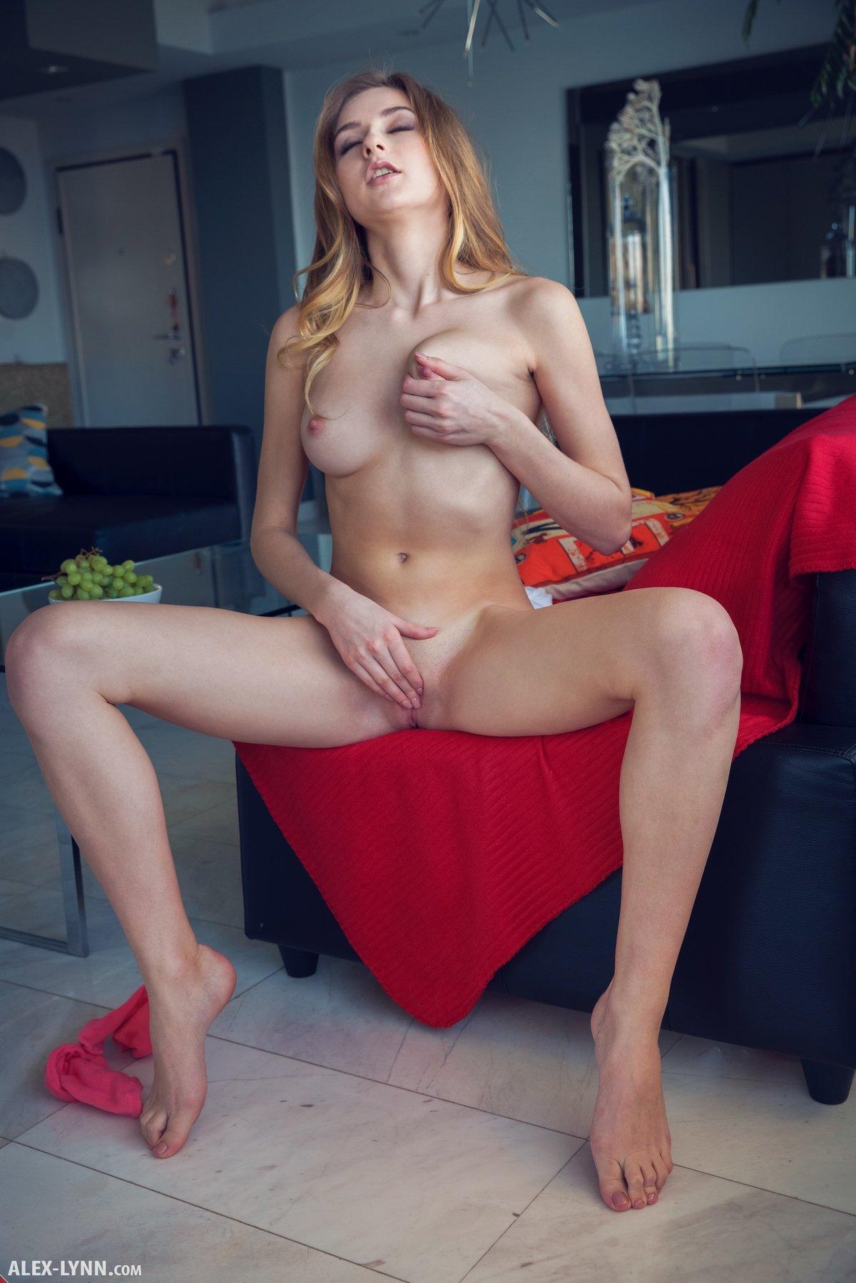 Хорошенькая барышня с рыжими волнистыми волосами голая ест виноград
