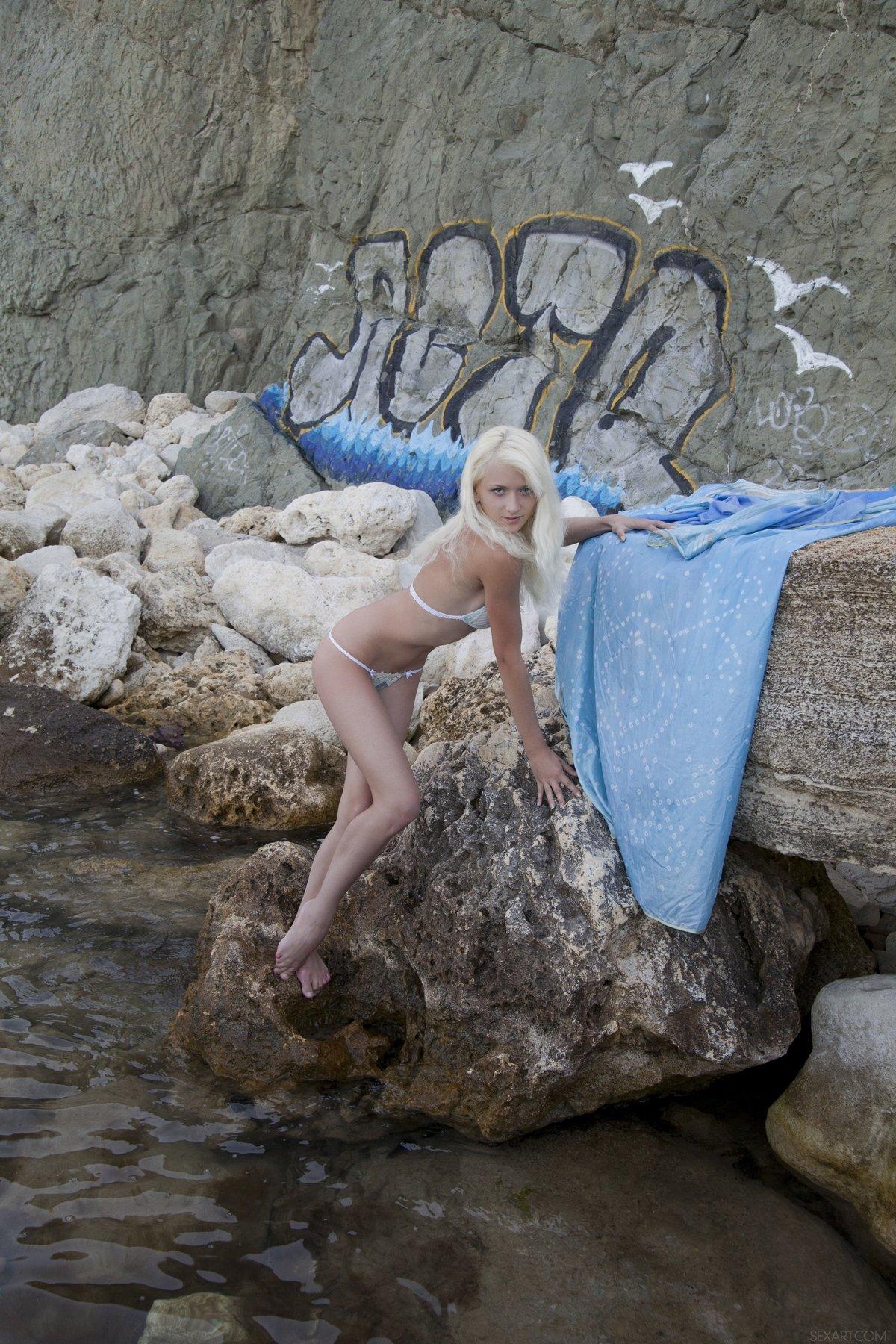 Игривая блонди с голубым парео на камнях у моря секс фото