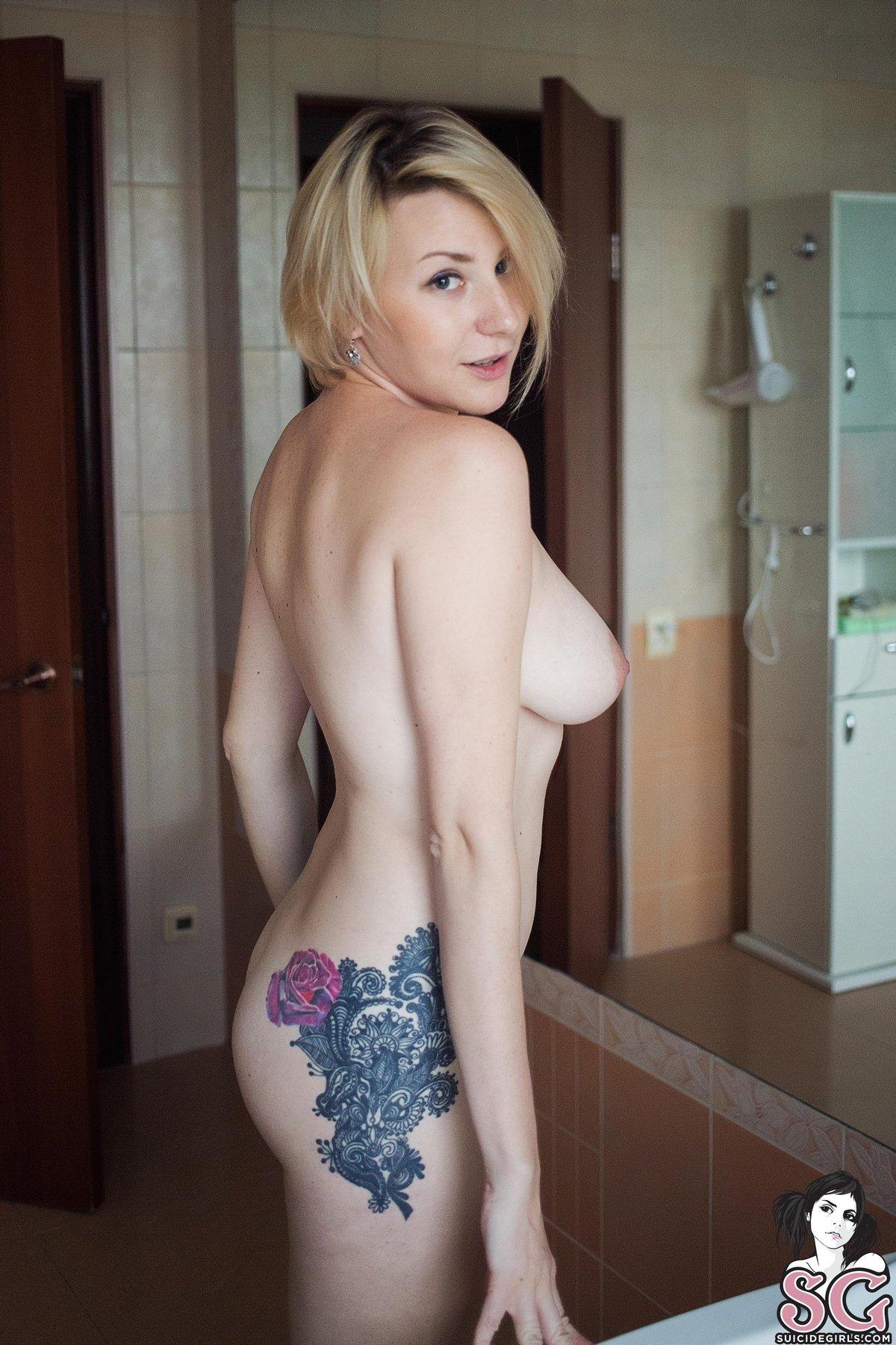 Светловолосая девушка с татуировкой на бедре под струями душа
