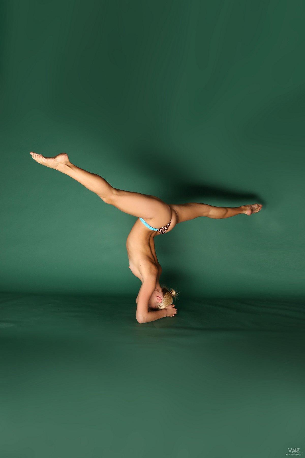 Обнаженная гимнастка стоит на голове