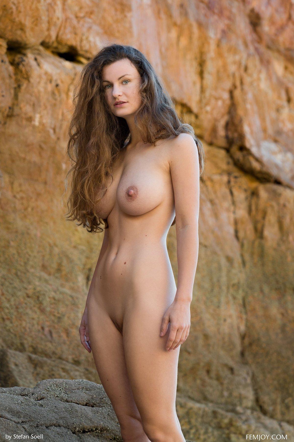 Девица с прекрасными титьками обнаженная около скалы смотреть эротику