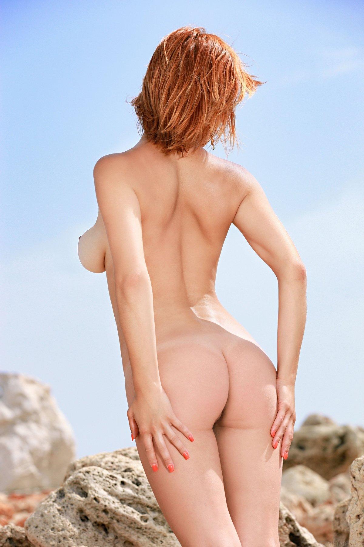 Раздетая рыжеволосая девушка ест вишни сидя на камнях секс фото