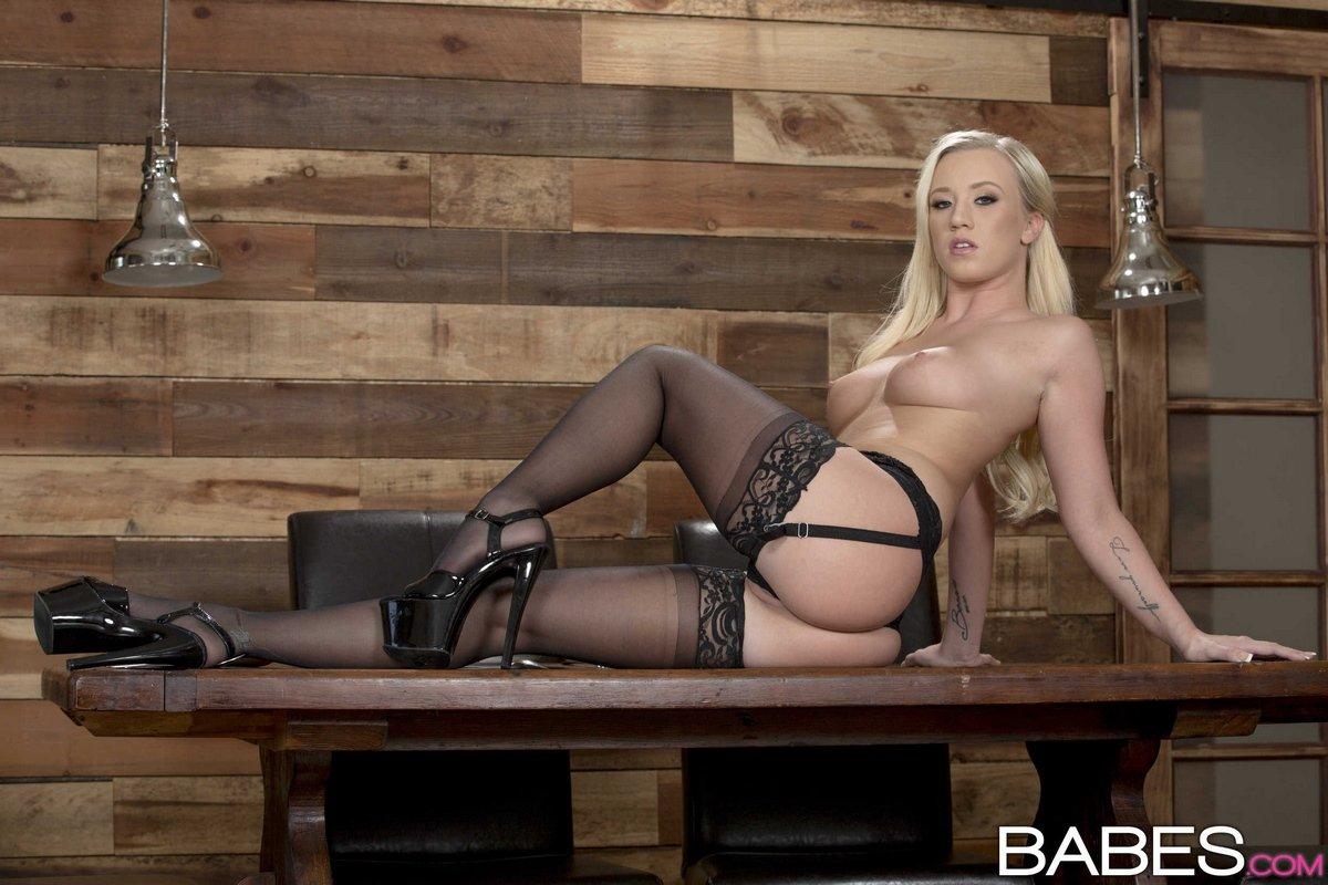 Красотка блондинка в чулках позирует на столе