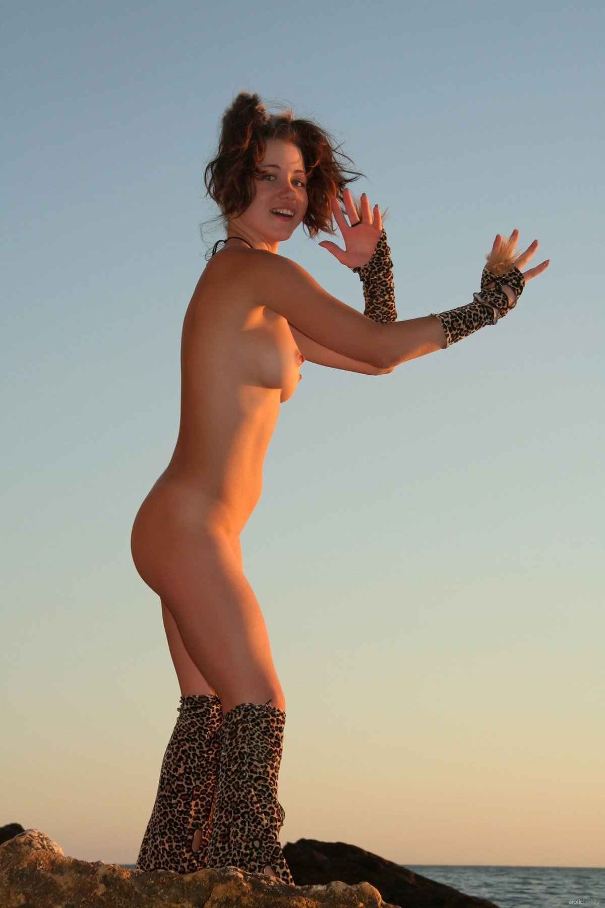 Леди в леопардовом костюме недалеко от скалы
