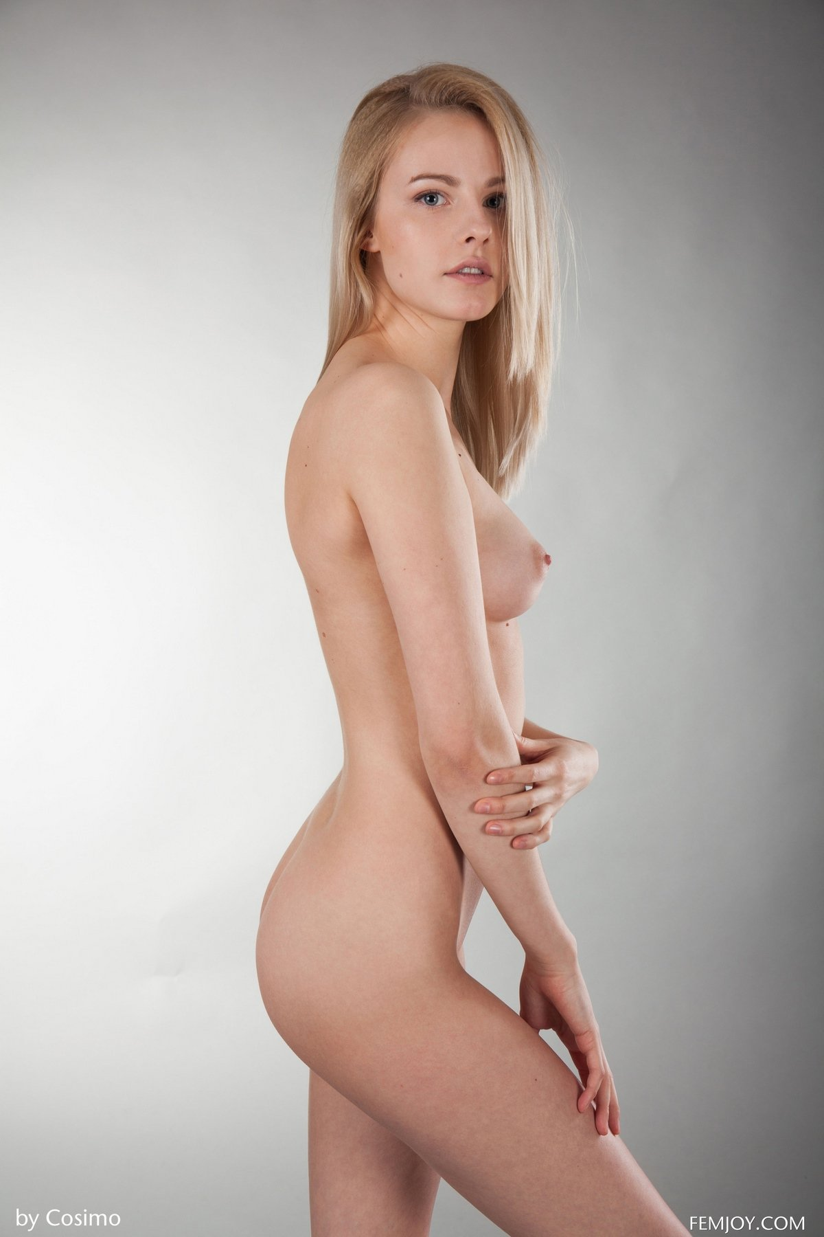 Стройная блондинка скинула маечку и фотографируется в студии