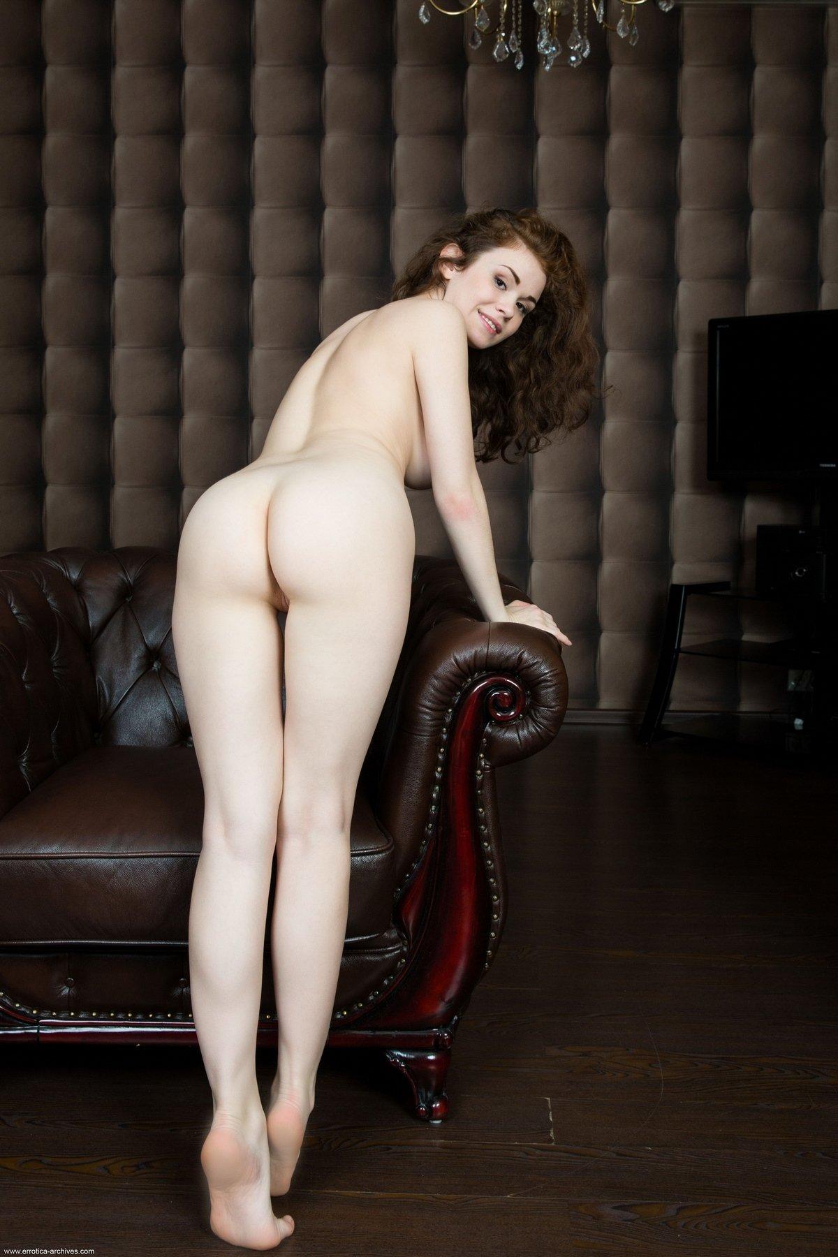 Голая молодая женщина в кожаном кресле