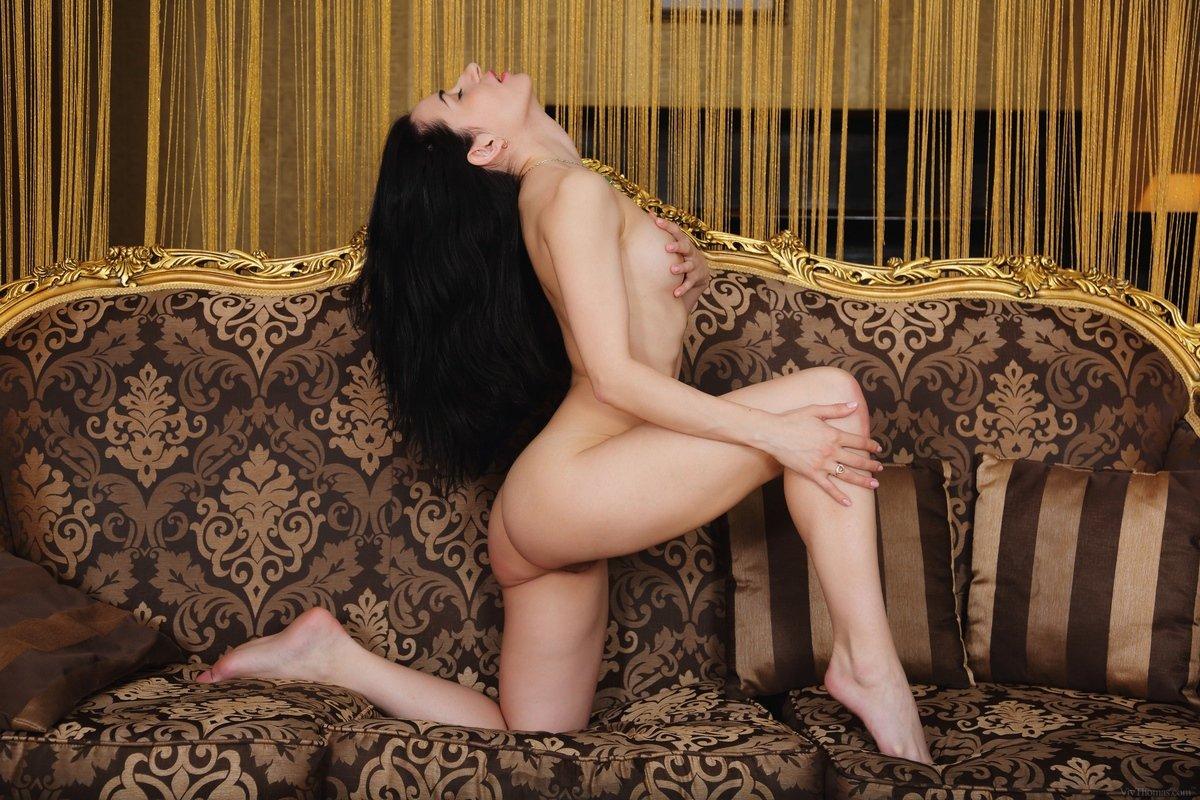 Голая модель с темными волосами поднимает симпатичные ноги на тахте