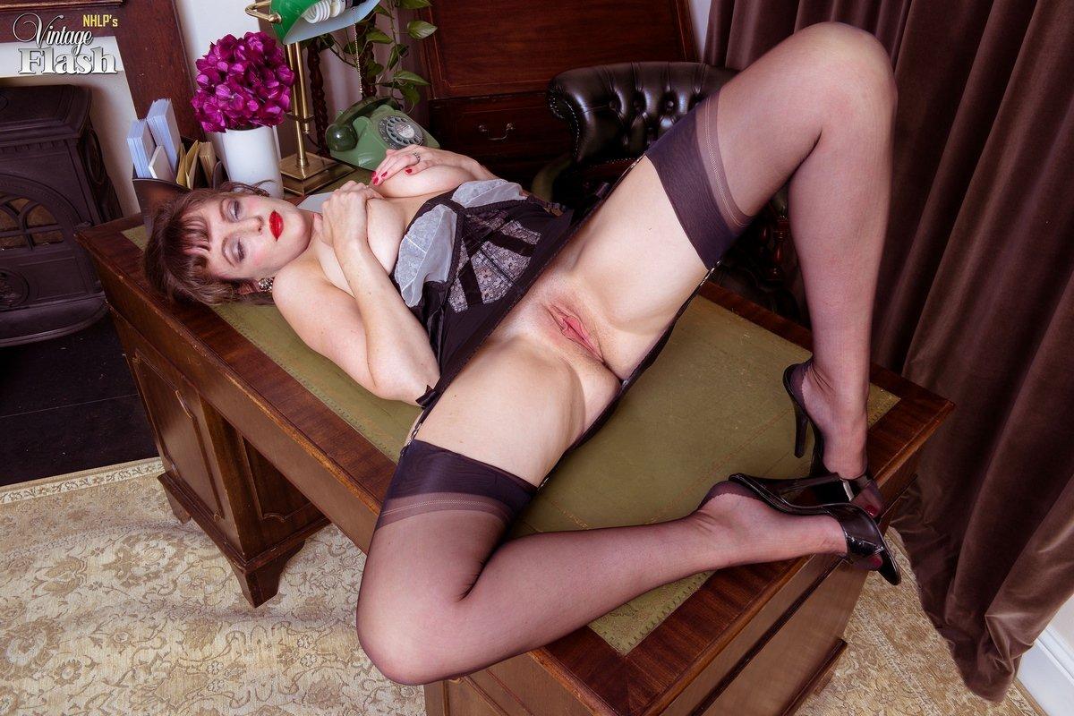 Возбуждённая особа женского пола в чулках позирует на столе