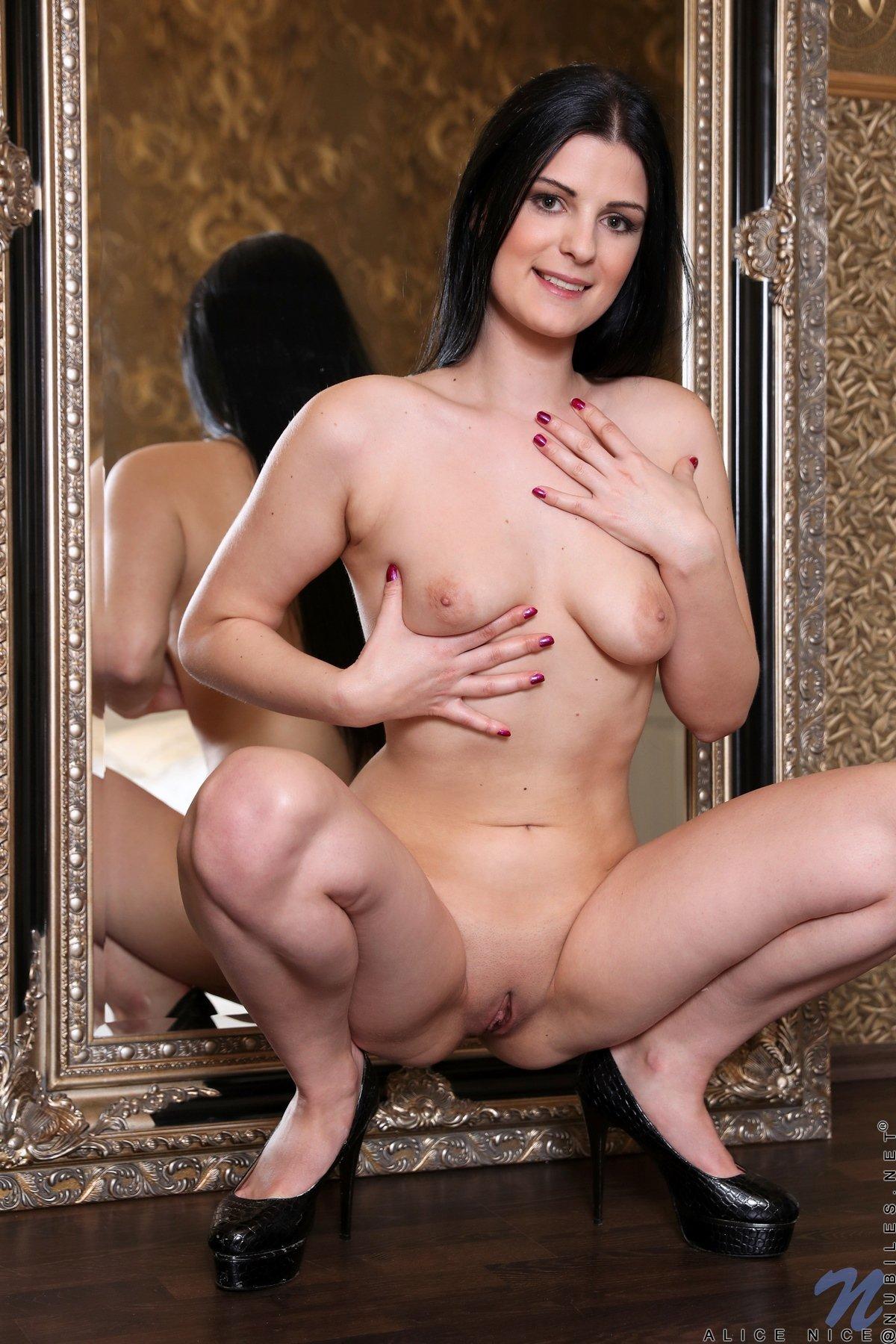 Брюнетка снимает шортики перед зеркалом