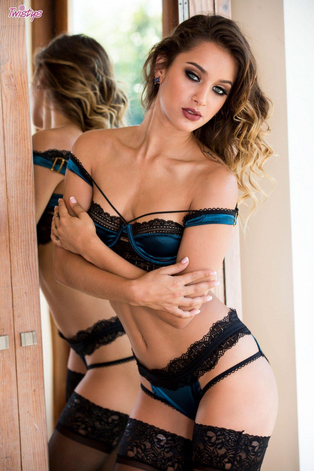 Сексуальная модель в шикарном белье и чулочках стоит перед зеркалом