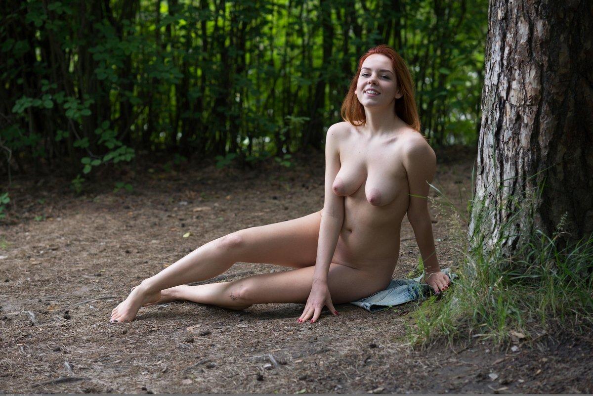 Рыжеволосая девушка гуляет в лесу без трусиков