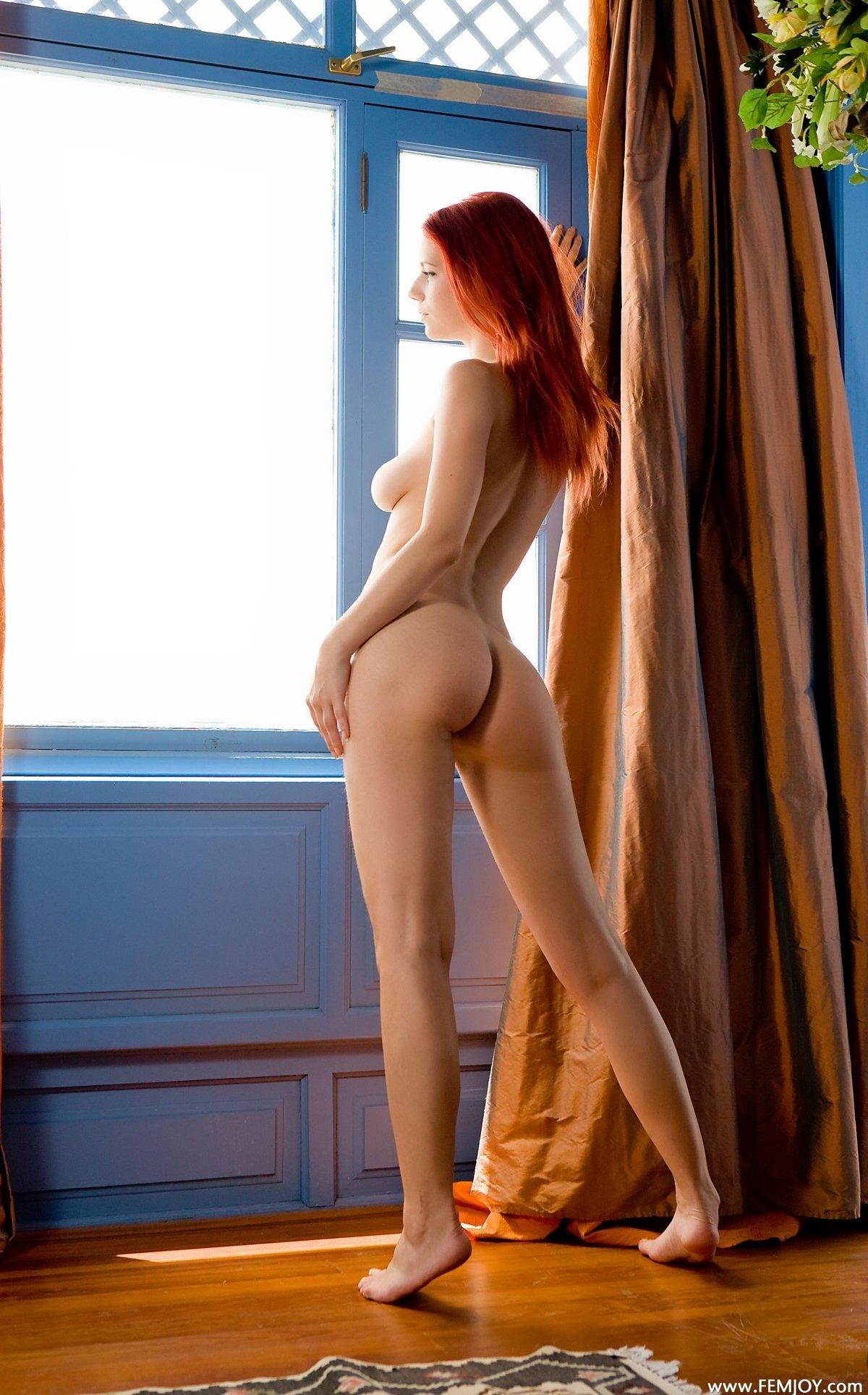 Голая девица с ярко рыжими волосами у окна