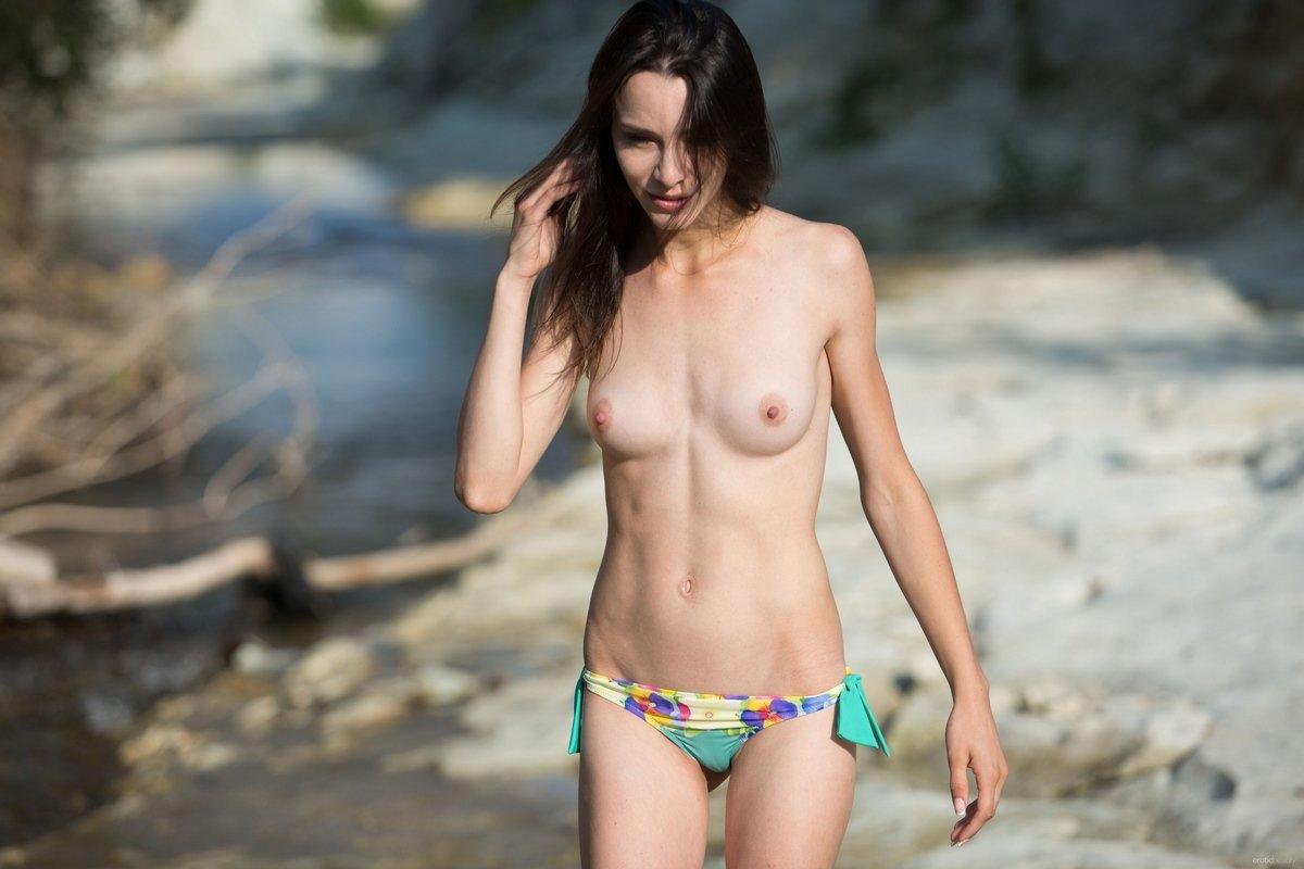 Худенькая брюнетка снимает яркий купальник возле ручья