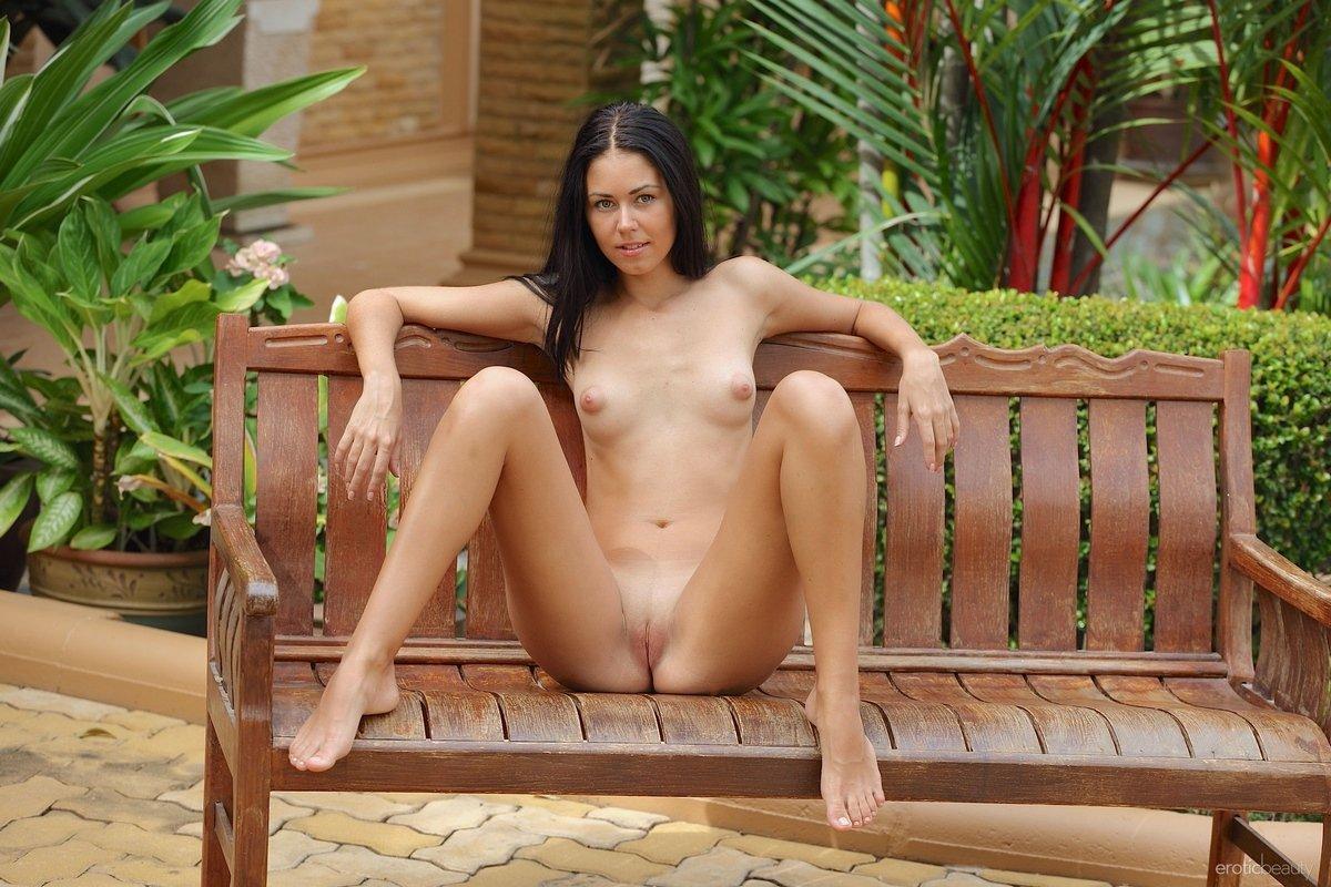 Изящная девушка голая на скамейке в саду