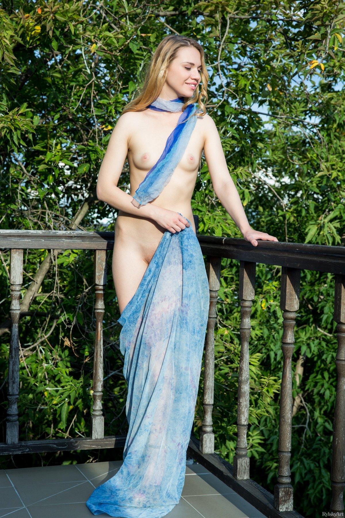 Обнаженная светлая модель с голубым парео на балконе
