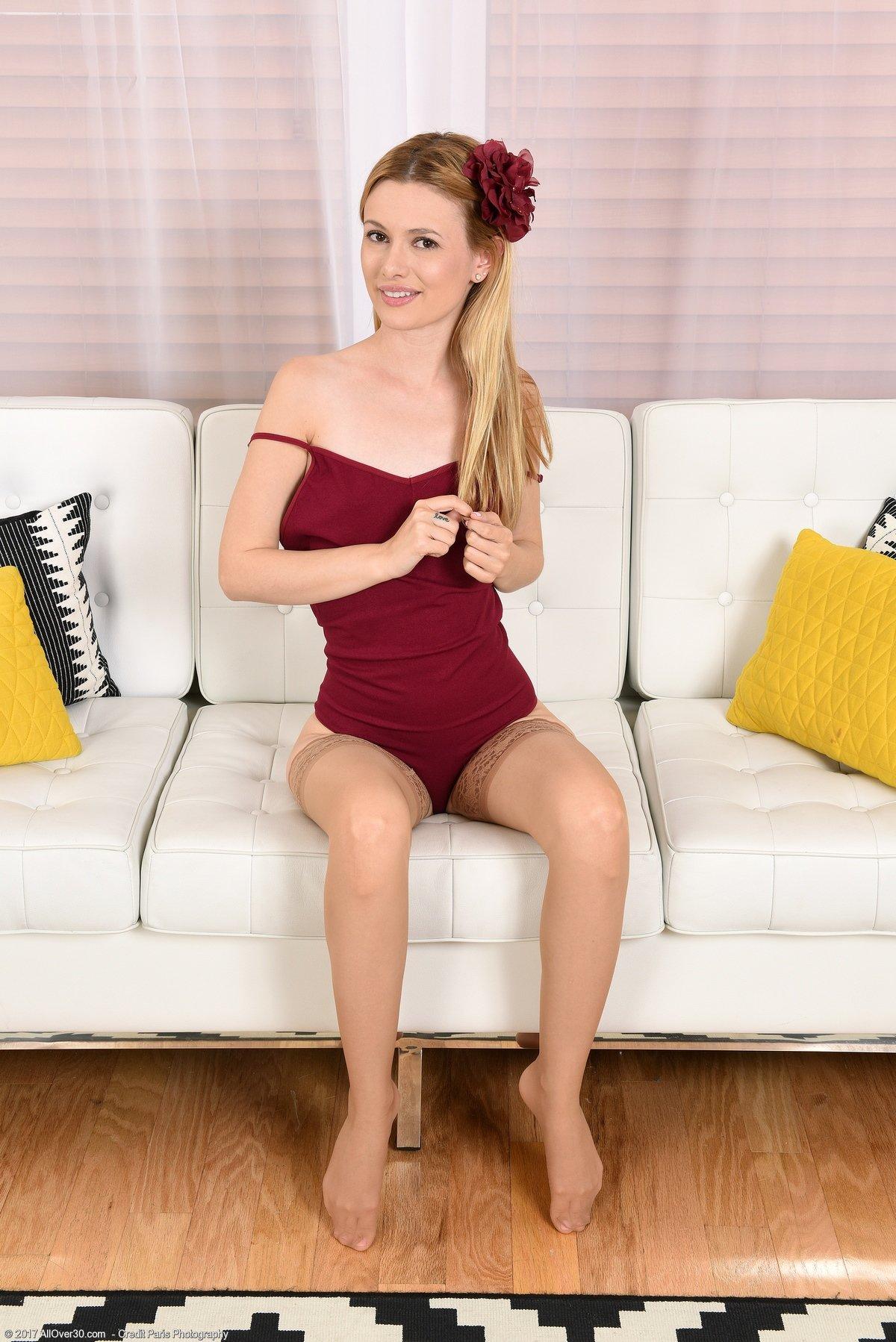 Женщина с цветком в волосах раздвигает ноги в чулках