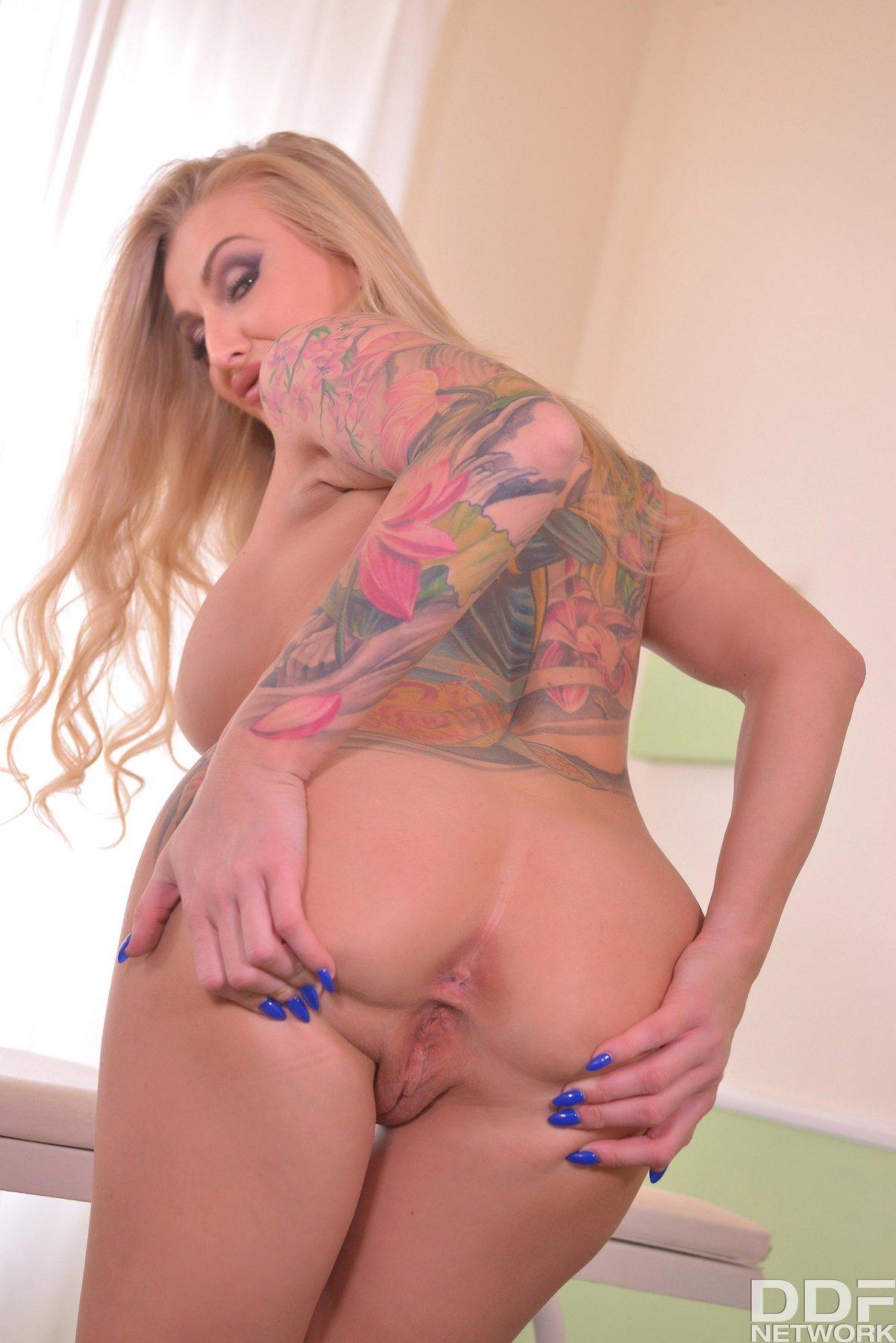 Блондинка в белье красного цвета показывает татуировки
