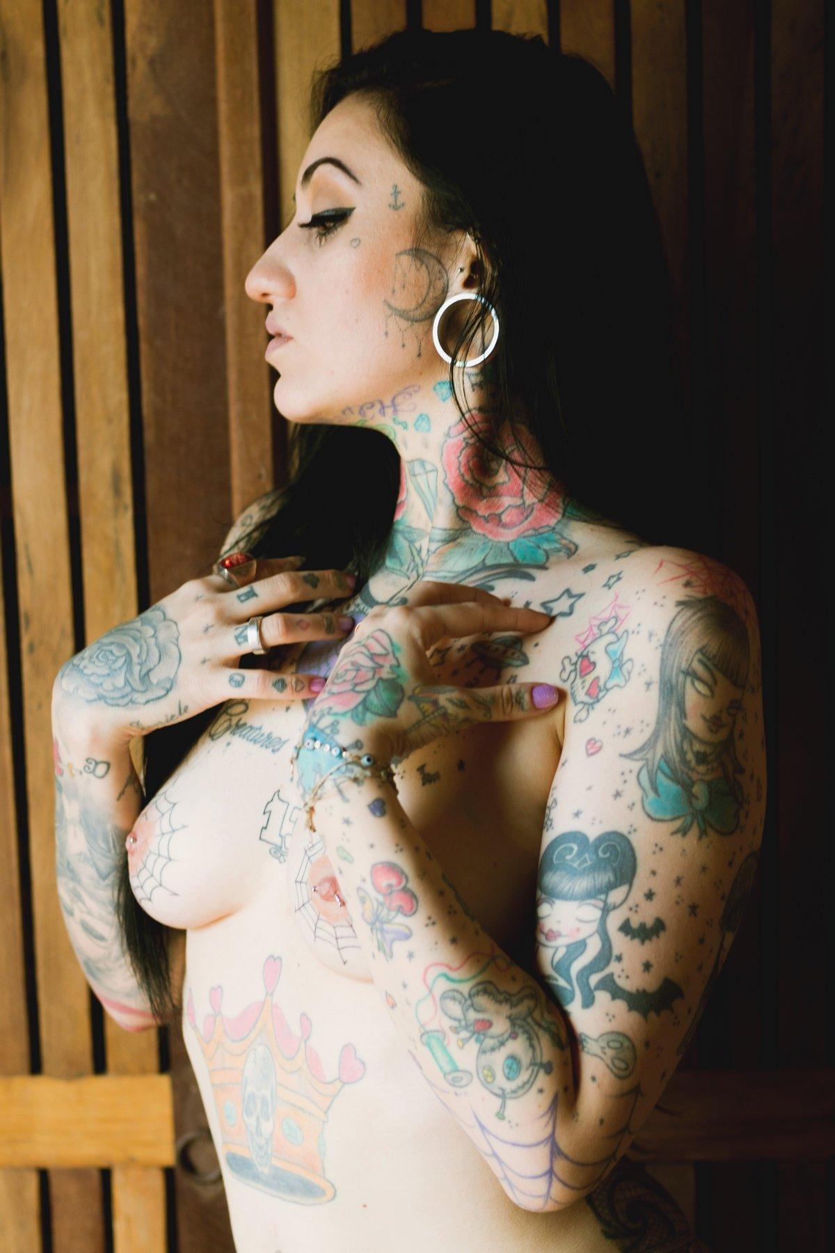 Обнаженная модель с темными волосами с цветными татухами на теле