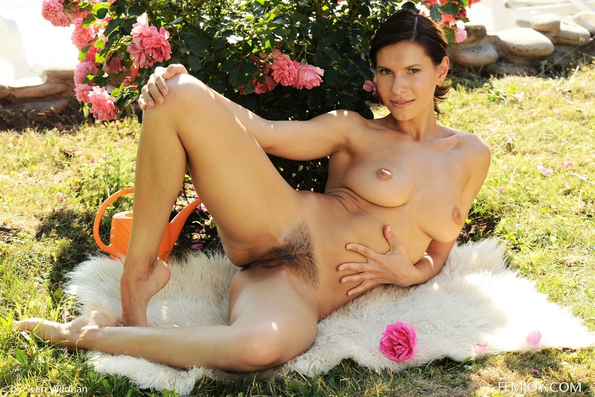Голая шатенка поливает розы в саду секс фото