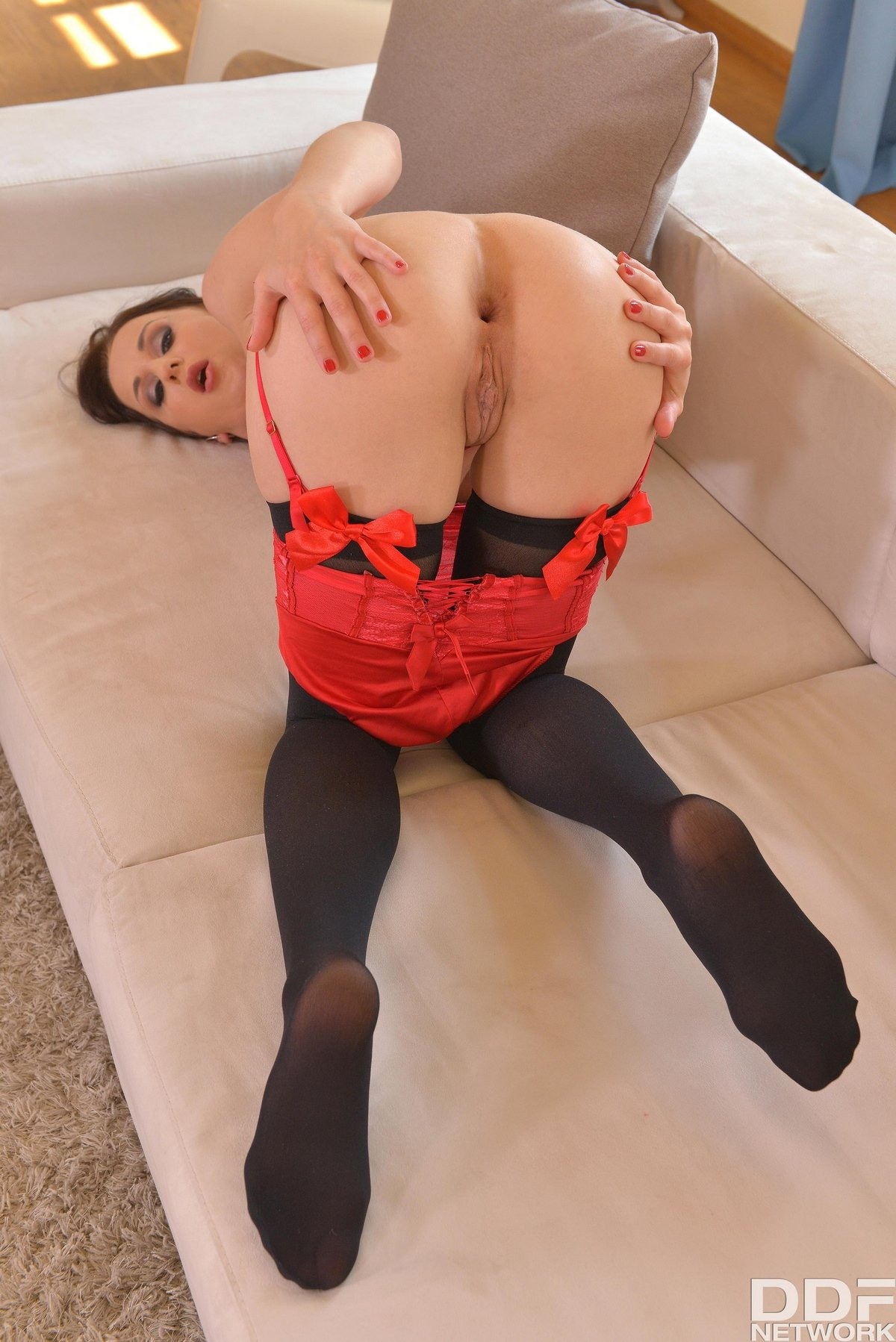 Женщина показывает длинные ноги в чулках с красными бантиками